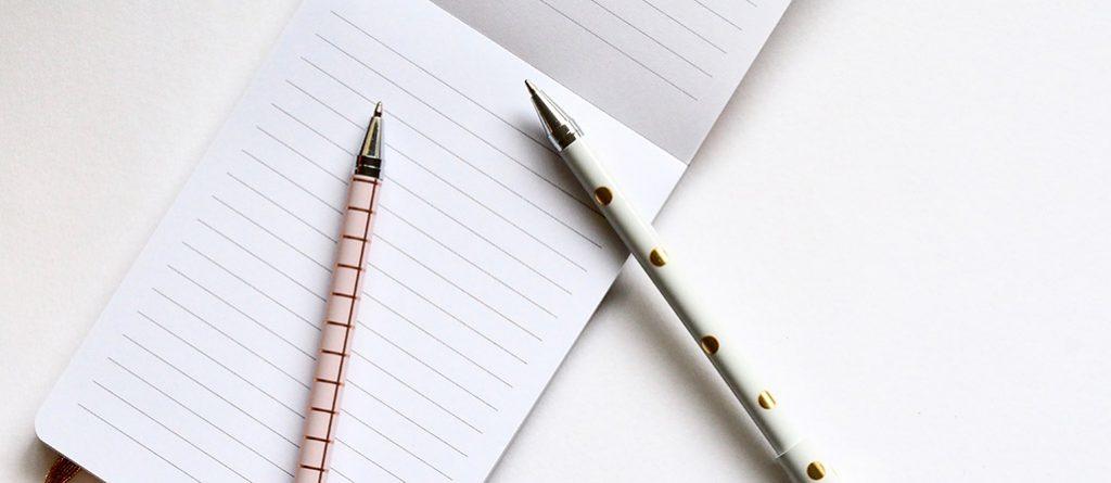 Bloco de notas e canetas