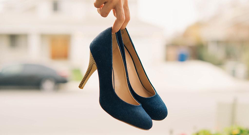 Mãos a segurar sapatos azuis