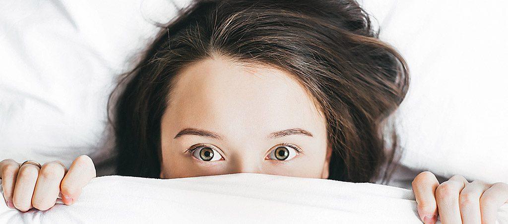 Mulher na cama de olhos abertos
