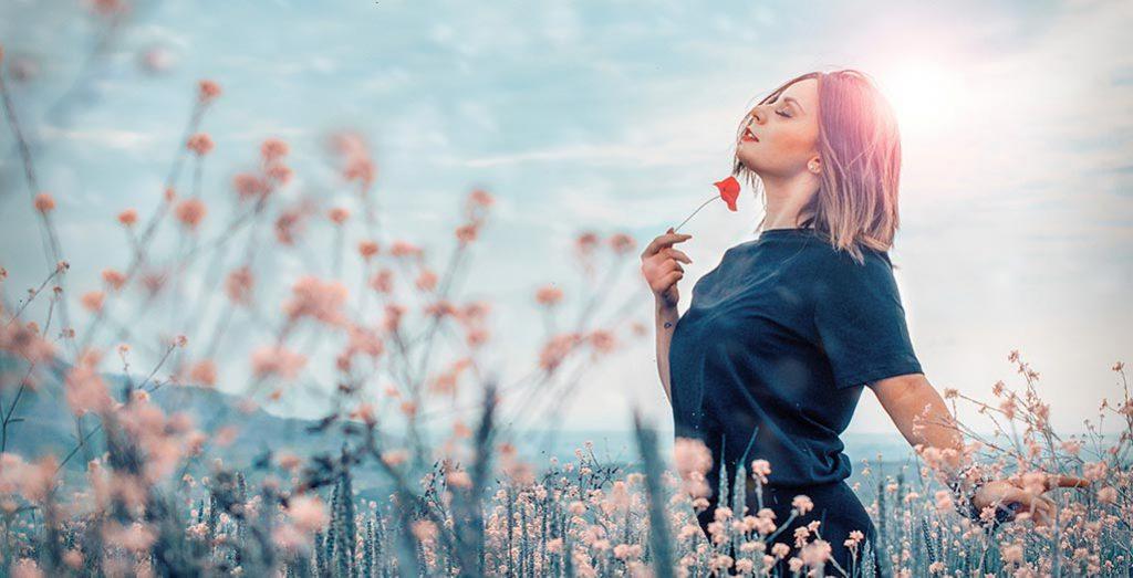 Mulher feliz num campo com flores